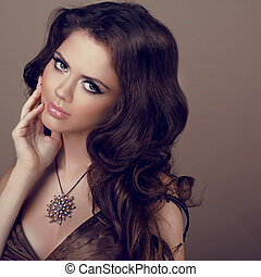 Portrait of Beautiful woman with curly hair and evening make-up. Jewelry and Beauty. Fashion girl photo