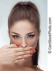 Portrait of beautiful woman with hand on lips over gray ...