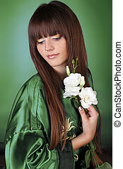 Portrait of Beautiful Woman with Healthy Long Hair over green