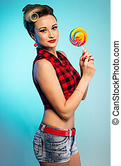 Portrait of beautiful woman with lollipop, dressed in pin-up style.