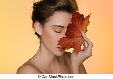 woman with maple autumn leaves on yellow background