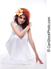 Portrait of beautiful woman with spring flower in hair on white