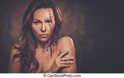 Portrait of beautiful woman with creative colored makeup on a dark background.
