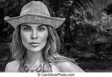 Portrait of beautiful woman with straw hat on a sunny day