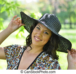 Portrait of beautiful woman with straw hat smiling
