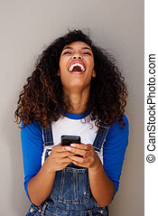 beautiful young african american woman laughing with cellphone