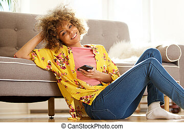 beautiful young african american woman sitting on floor and using cellphone