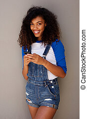 beautiful young african american woman with curly hair holding mobile phone