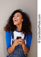 beautiful young african woman laughing with cellphone