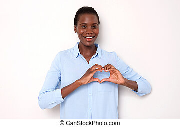 beautiful young african woman smiling with heart shaped hand sign on white background
