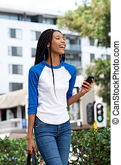 beautiful young african woman walking outdoors in the city with cellphone