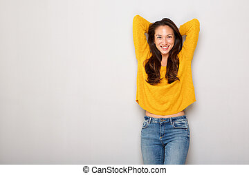 beautiful young asian woman smiling with arms crossed against gray background