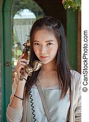 woman talking on vintage telephone