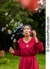young asian woman with Carmen red dress blowing bubble