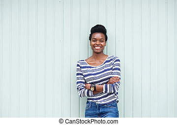 beautiful young black woman smiling with arms crossed