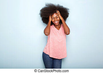 beautiful young black woman smiling with hands in hair