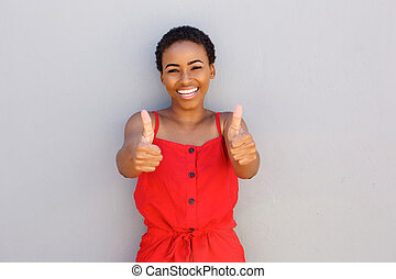 beautiful young black woman smiling with thumbs up hand gesture
