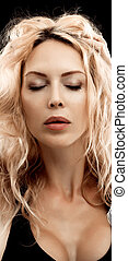 Portrait of beautiful young blond woman on black