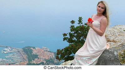 Portrait Of Beautiful Young Blond Woman With Wind Blowing In Her Hair Sitting On A Rock - Monaco Aerial View