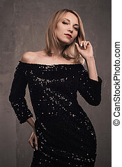 Portrait of beautiful young blonde girl in black dress.