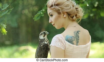 Portrait of beautiful young blonde in pink dress with a falcon in hands, close-up