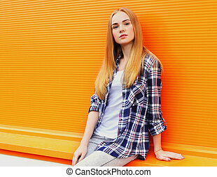 Portrait of beautiful young blonde woman on city street over orange wall background