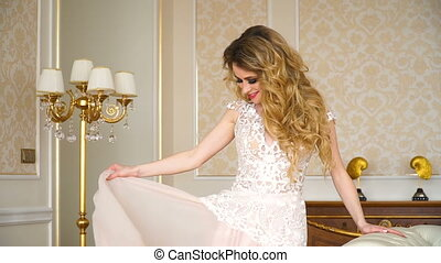 Portrait of beautiful young bride. A girl is posing in a hotel room. The lady is spinning in her wedding dress
