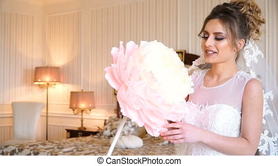 Portrait of beautiful young bride. A girl is posing in a hotel room. A lady is sitting with a paper flower by the window. bride waiting in hotel