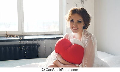 Portrait of beautiful young bride posing and smiling into camera Woman sits on the bed in bedroom