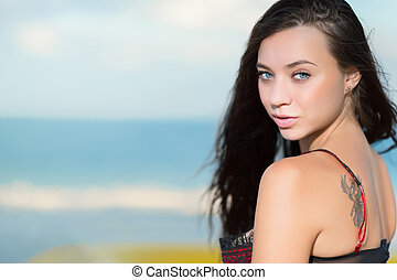 Portrait of beautiful young brunette with tattoo