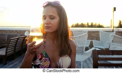 Portrait of beautiful young brunette woman drinking wine outdoors cafe at the sunset