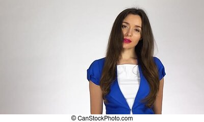 Portrait of beautiful young brunette woman against white background. 4K video