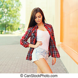 Portrait of beautiful young brunette woman in a city on white background