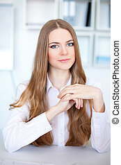 Portrait of beautiful young business woman sitting at desk in bright office