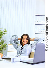 Portrait of beautiful young business woman thinking while relaxing at office