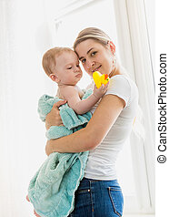 Portrait of beautiful young caring mother holding her baby in blue towel after washing in bath