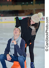 portrait of beautiful young couple ice skating on rink