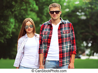 Portrait of beautiful young couple wearing a sunglasses and casual clothes outdoors in summer day