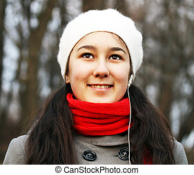 Portrait of beautiful young girl on background of the park