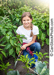 Portrait of beautiful young girl sitting in garden and spudding soil with growing vegetables