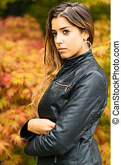 Portrait of beautiful young girl with a background of autumn leaves