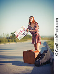 Portrait of beautiful young hippie woman hitchhiking on a ...