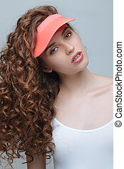 Portrait of beautiful young hipster woman in pink cap looking at camera