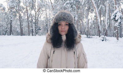 portrait of beautiful young in hat woman at winter snowy forest