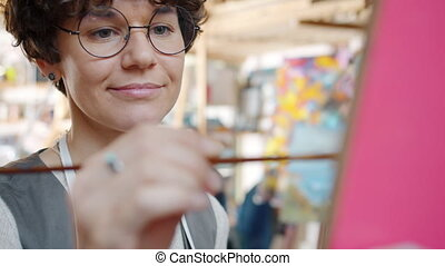 Portrait of beautiful young lady artist painting picture ...