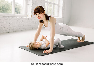 Portrait of beautiful young mother in white sports wear with her charming little baby girl doing exercises on the black mat in training session at gym