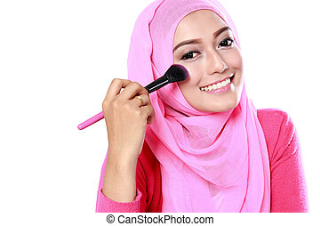 portrait of beautiful young muslim woman applying blush on with white background