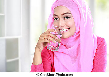 young muslim woman drink a glass of water