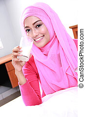 young muslim woman drinking a glass of milk