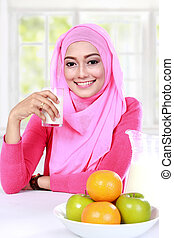 young muslim woman had a milk and fruits for breakfast -...